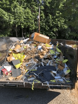 A picture of a junk removal trailer full of residential junk at a construction site clean up. This picture was taken in Gresham Oregon.